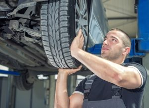 A mechanic is changing a tire on a automobile